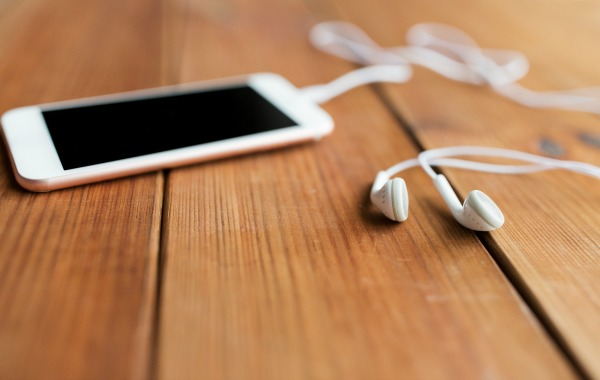 smartphone and earbuds for podcast listening